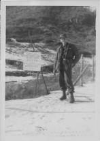 """Caption: refer pix #2 Jan 1, 1954 New Years Day. On the way back from the 25th Inf. Div. QM we went offcourse to take this pix. My first look at the DZ (Demilitarized) - No Man's Land-e Commies on the other side. That's snow on the ground and me, Natch! Sign hung on barbed wire reads """"South Limit Demil Zone Do Not Enter"""" & Korean writing. Armond Small"""