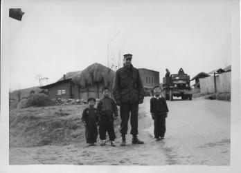 Don Feeney with children in the town of Tukto, near 48th MASH, January, 1954